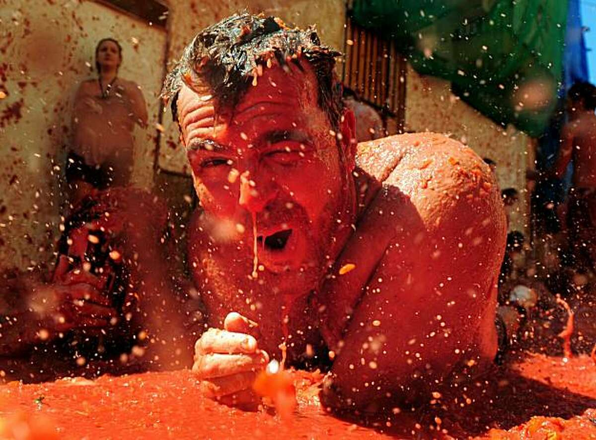 BUNOL, SPAIN - AUGUST 25: A reveller swims in tomato pulp during La Tomatina festival, the world's biggest tomato fight on August 25, 2010 in Bunol, Spain. More than 45000 people from all over the world descended on the small Valencian town to participate in this year's La Tomatina festival, with the local town hall estimating that over 100 tons of rotten and over-ripe tomatoes were thrown. (Photo by Jasper Juinen/Getty Images) *** BEST PIX ***