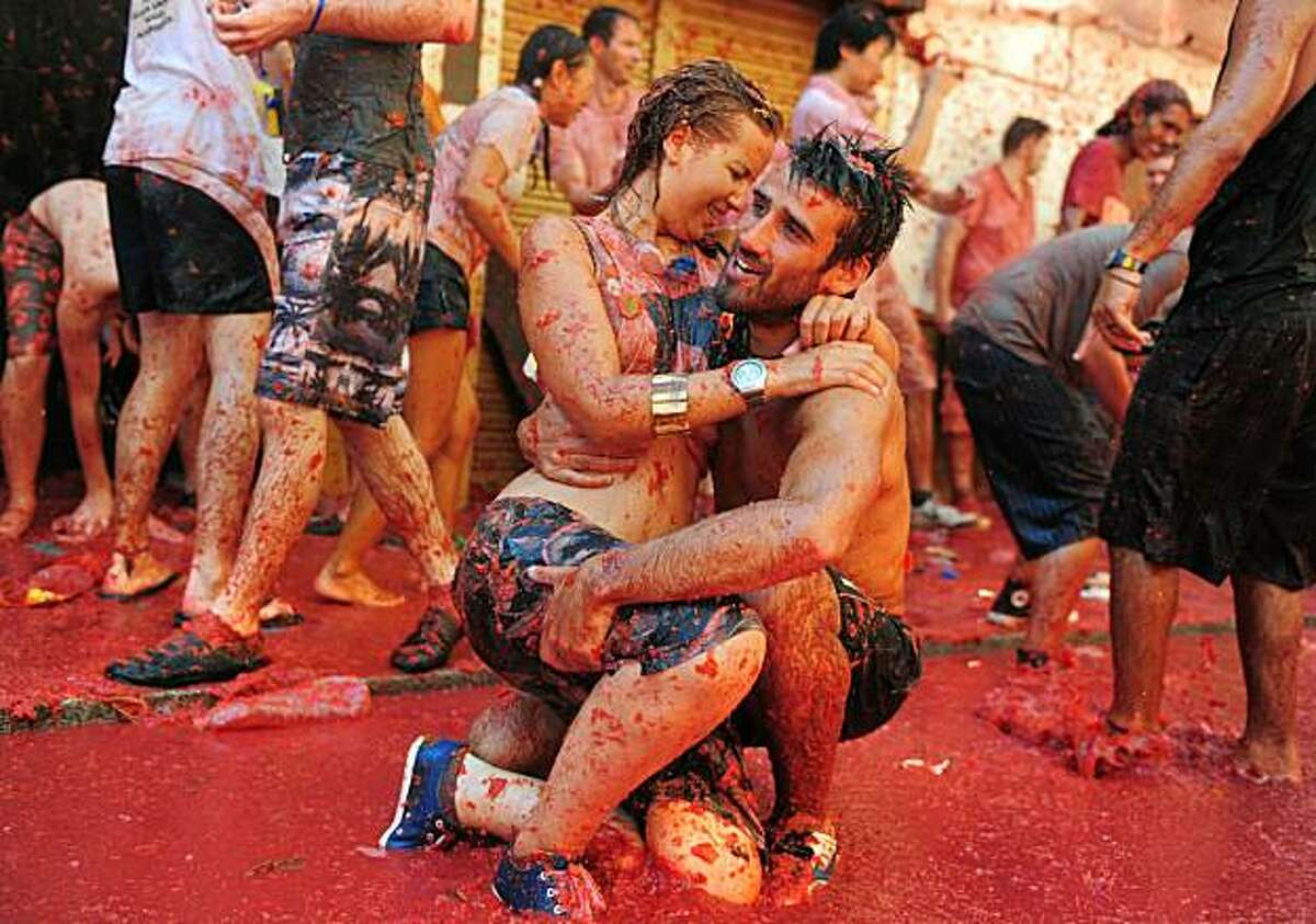 BUNOL, SPAIN - AUGUST 25: Revellers cuddle in tomato pulp during La Tomatina festival, the world's biggest tomato fight on August 25, 2010 in Bunol, Spain. More than 45000 people from all over the world descended on the small Valencian town to participate in this year's La Tomatina festival, with the local town hall estimating that over 100 tons of rotten and over-ripe tomatoes were thrown.