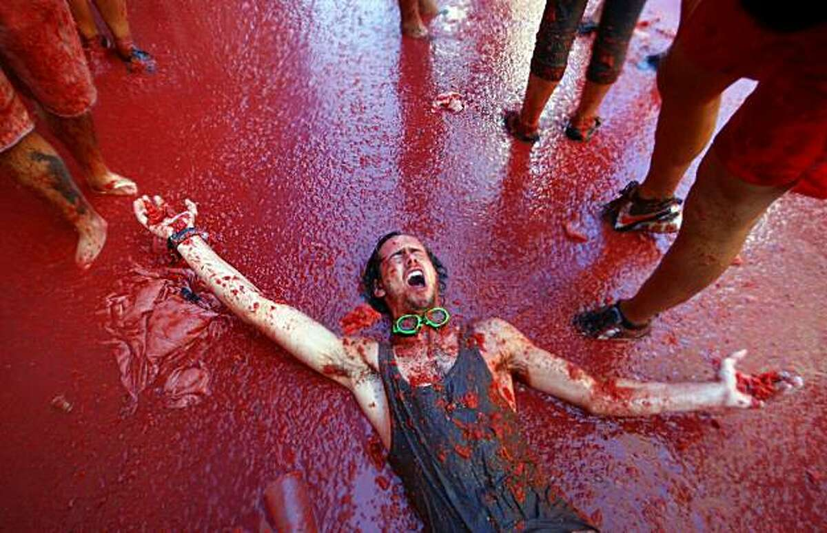 TOPSHOTS A man is pelted with tomatoes during the