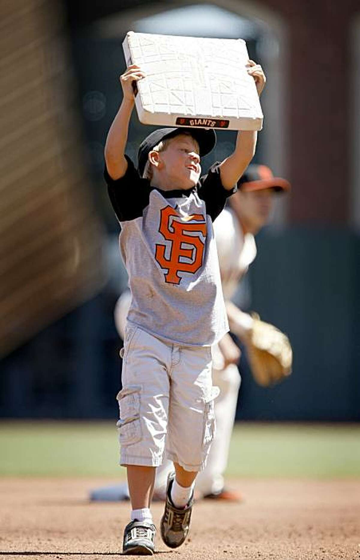 Little Boy's Dream - 2:05 p.m. -AT&T Park, San Francisco While shooting the Giants game, I saw seven year old Connor Fingles run out on the field to change second base for his birthday. Now that's what I call a birthday present.... Camera settings: Canon EOS-1D MkIII, ISO 250, 1/1000, f4, 400mm