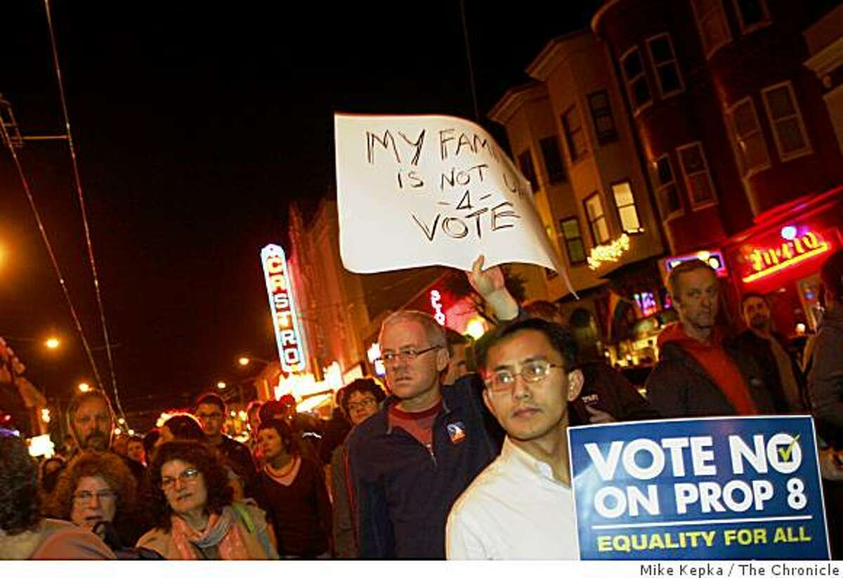 Kevin McCarthy, holding sign, and his husband David Bui, of San Francisco, join a crowd of thousands as they head down Castro Street during a march to protest the passage of Prop. 8 in San Francisco, Calif., on Friday Nov. 7, 2008.