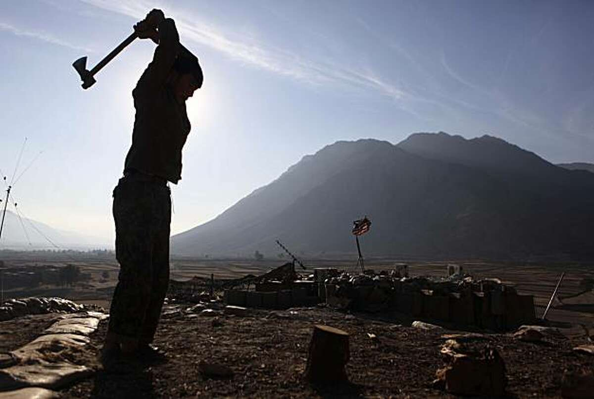 An Afghan National Army soldier chops wood at Badel Combat Out Post in Kunar province in eastern Afghanistan near the border of Pakistan on Saturday, Jan. 1, 2011.