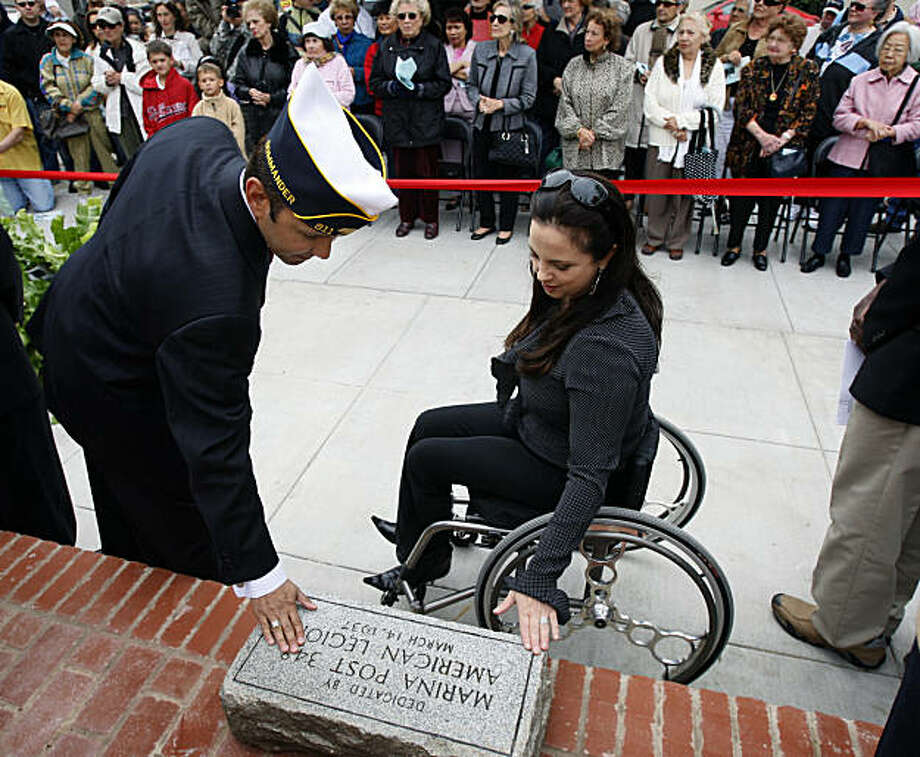Michael Gerold, commander of American Legion Post 911, and Supervisor Michela Alioto-Pier touch a stone plaque that will be reinstalled at the Moscone Recreation Center in San Francisco, Calif., on Saturday, July 19, 2008. The plaque was originally installed at the historic building in 1937 to honor Marina District residents who fought in World War I and II. Photo by Paul Chinn / The Chronicle Photo: Paul Chinn, The Chronicle