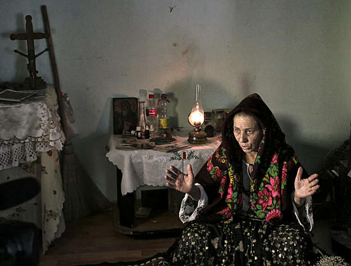 Romanian Bratara Buzea, 63, who was imprisoned for witchcraft under communist dictator Nicolae Ceausescu's repressive regime, speaks during an interview with The Associated Press in Mogosoaia, Romania, Wednesday, Jan. 5, 2011. Trouble is brewing for Romania's witches, whose toil is being taxed for the first time despite their threats of putting curses on the government. Also being taxed for the first time are fortune tellers, who probably saw this coming.