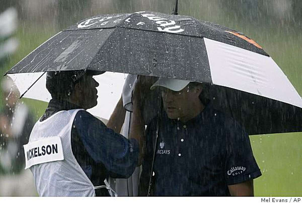 Phil Mickelson waits under his umbrellas while caddie Jim MacKay dries one of his clubs on the second tee box during the third round of the U.S. Open Golf Championship at Bethpage State Park's Black Course in Farmingdale, N.Y., Saturday, June 20, 2009. (AP Photo/Mel Evans)
