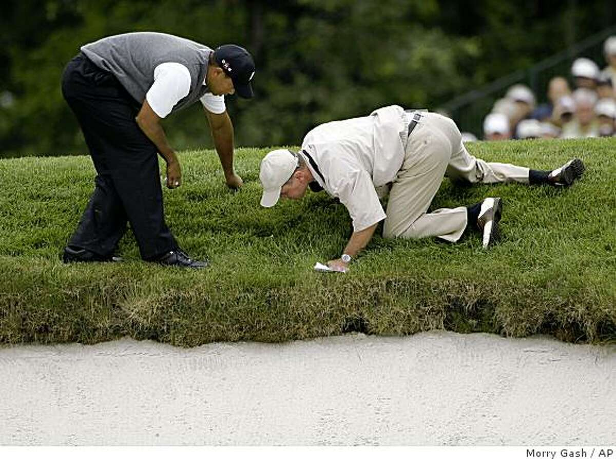 An official examines the rough off the 15th green before giving Tiger Woods, left, a ruling on his ball during the first round of the U.S. Open Golf Championship at Bethpage State Park's Black Course in Farmingdale, N.Y., Friday, June 19, 2009. Play was suspended on Thursday because of inclement weather. (AP Photo/Morry Gash)