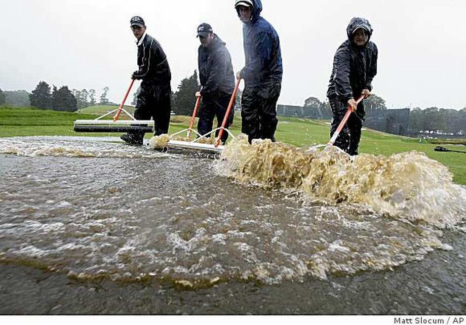 Course workers roll water off the 18th fairway at the Bethpage State Park's Black Course in Farmingdale, N.Y., Thursday, June 18, 2009. Play was canceled at the U.S. Open Golf Championship because of inclement weather and will resume on Friday. (AP Photo/Matt Slocum) Photo: Matt Slocum, AP