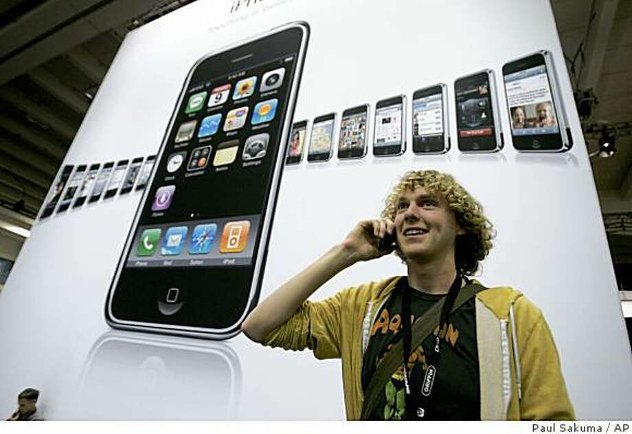 Attendee Wil Gieseler talks on his Apple iPhone in front of a iPhone poster at the MacWorld Conference in San Francisco, Tuesday, Jan. 15, 2008.  Apple Inc. is scheduled to report first-quarter financial results after the market closes Tuesday, Jan. 22, 2008. (AP Photo/Paul Sakuma) Photo: Paul Sakuma, AP