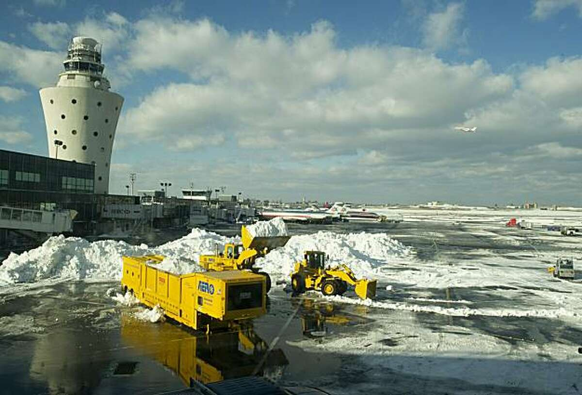 Workers remove snow from the tarmac at New York's LaGuardia Airport on December 28, 2010. The US northeast began to shake off the icy grip of one of the biggest blizzards in years, but beleaguered travelers faced at least another day of headaches in New York airports.