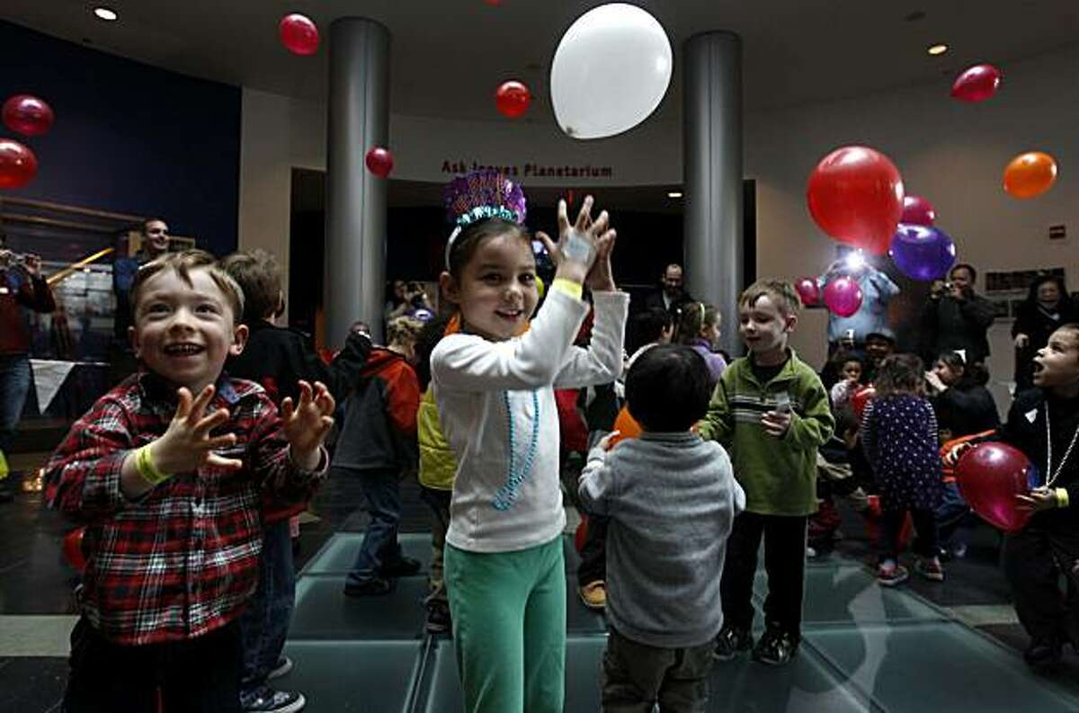 Balloons float down from the ceiling and into the arms of excited children celebrating the New Year at the Chabot Space and Science Center in Oakland on Friday. The 11th annual daytime celebration let kids ring in 2011 as it turned midnight somewhere else.