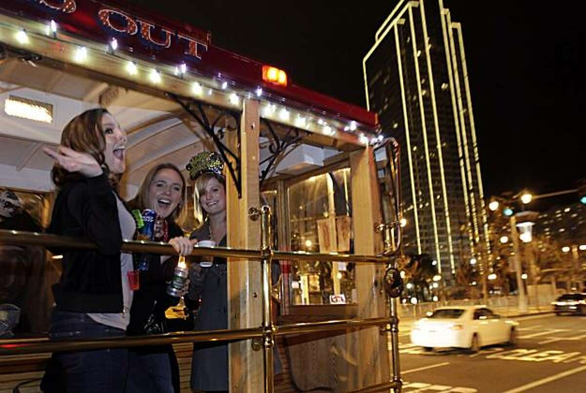 New Year's revelers enjoy a moving party aboard a Bauer Limousine Cable Car replica on the Embarcadero of San Francisco as midnight approaches Friday.