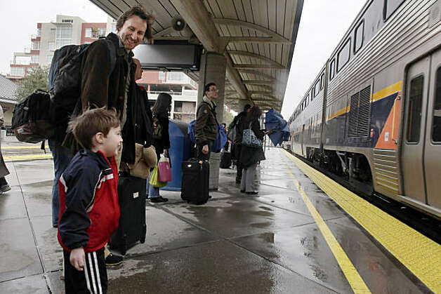 Barton Saunders smiles down at his son, Hayden Saunders, 3, as their Capitol Corridor Amtrak train to Sacramento arrives at the Emeryville, Calif., station on Tuesday, December, 28, 2010. The father and son from Los Angeles had visited friends in San Francisco, and were on their way to visit friends in Sacramento. While high-speed rail in California is getting all the attention, the state's lower-speed intercity trains are seeing a boom in popularity. Trains like the Capitol Corridor, shown here on Thursday, December 23, 2010,  in Emeryville, Calif., have seen a double digit rise in passengers. Photo: Carlos Avila Gonzalez, The Chronicle