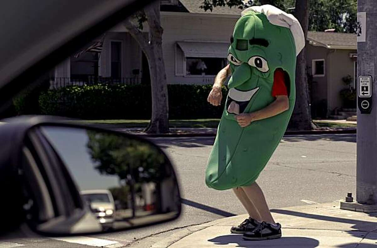 A Pickle - 12:19 p.m. - Livermore. I was heading to the public library for an assignment, when I pulled up to a stop-light out jumped Mr. Pickles. I rolled down the window and shot a few frames of the character in front of a local sandwich shop. Camera settings: Canon 5D MkII, ISO 200, 1/250, f8, 85mm