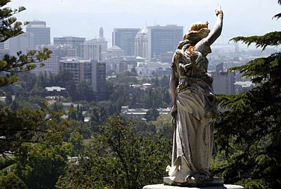 Angel - 1:20 p.m. - Oakland.   While driving through Oakland's Mountain View Cemetery trying to take a deer photo, I had to stop and make this image of an angel perched above a family plot with the city skyline as a background. What a peaceful setting.   Camera settings: Canon 5D MkII, ISO 200, 1/250, f13, 200mm Photo: Lance Iversen, The Chronicle