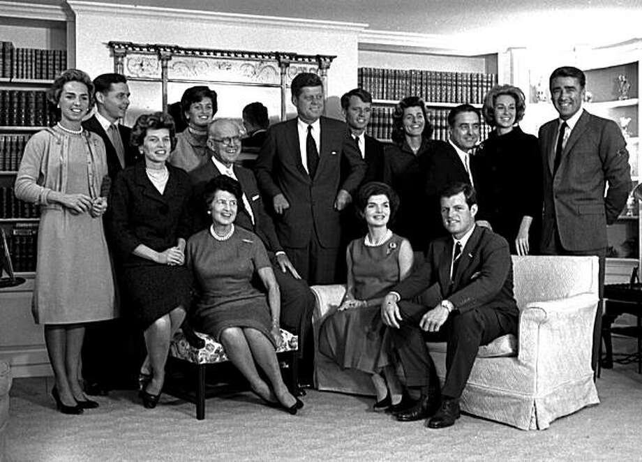 FILE - In this Nov. 9, 1960 file photo, President-elect John F. Kennedy, center, is surrounded by members of his family in the living room of the home of Joseph P. Kennedy, in Hyannisport, Mass.  Standing, from left, Ethel Kennedy; Steve Smith and wife, Jean Kennedy; Senator Kennedy; brother Robert, campaign manager; sister, Patricia Lawford; Sargent Shriver; brother Ted's wife, Joan; and British actor Peter Lawford.  In foreground, seated from are:  Eunice Shriver, sister; mother Rose Kennedy; father, Joseph; Jacqueline Kennedy, wife of John; and Ted Kennedy, brother of the president-elect.  (AP Photo, file) Photo: AP