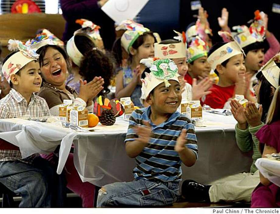 Kindergartners at Mission Education Center applaud after a performance by schoolmates before a Thanksgiving meal.  The youngsters from kindergarten through 2nd grade, all of whom just immigrated to the United States in the past year, were treated to a brief performance by each class then sat down to a traditional Thanksgiving meal. Photo: Paul Chinn, The Chronicle