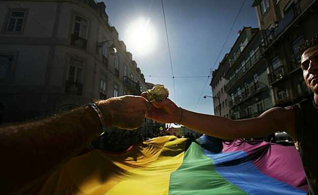 A man hands a rose to another man during the Gay Pride Parade in Lisbon, ...