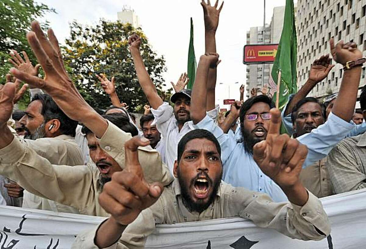 FILE - Pakistani Muslim men march during a demonstration in Karachi on May 18, 2008 to protest against Danish cartoons of the Prophet Mohammed. At least 17 Danish dailies reprinted one of the cartoons in February, vowing to defend freedom of expression a day after police in Denmark foiled a plot to murder the cartoonist. Islamic nations are mounting a campaign for an international treaty to protect religious symbols and beliefs from mockery _ essentially, a ban on blasphemy.