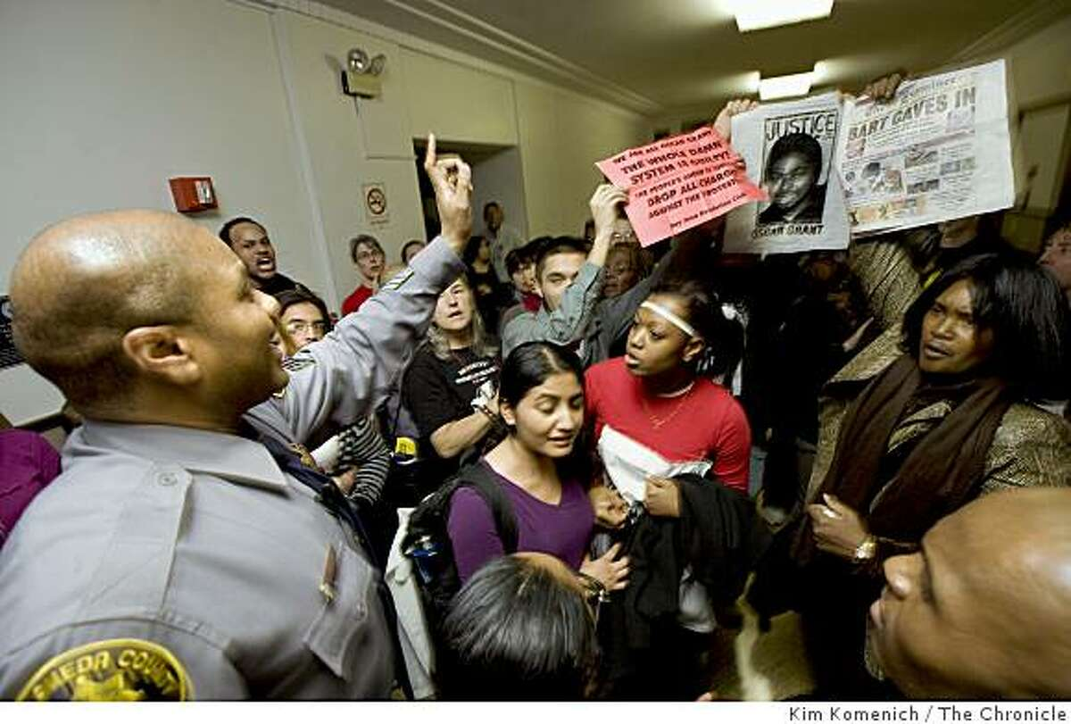 Alameda County Sheriffs Sgt. Darrell Burnett asks the crowd to remove signs outside the bail hearing for BART Officer Johannes Mehserle on Friday, January 30. 2009.