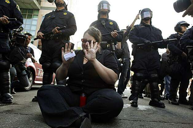 A woman who declined to give her name sits in front of a line of Oakland Police officers on 12th Street in Oakland calling for restraint from protesters and police alike. Reaction after the verdict in the Johannes Mehserle trial is announced on Thursday, July 8, 2010. Mehserle was convicted of involuntary manslaughter in the shooting of Oscar Grant at the Fruitvale BART station on January 1, 2009. Photo: Carlos Avila Gonzalez, The Chronicle