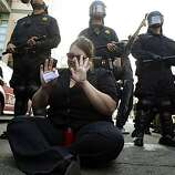 A woman who declined to give her name sits in front of a line of Oakland Police officers on 12th Street in Oakland calling for restraint from protesters and police alike. Reaction after the verdict in the Johannes Mehserle trial is announced on Thursday, July 8, 2010. Mehserle was convicted of involuntary manslaughter in the shooting of Oscar Grant at the Fruitvale BART station on January 1, 2009.