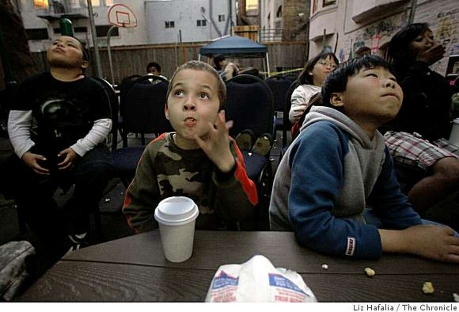 "Left to right--Juan Martinez, 8 years old, Ethan Chandler, 7 years old, and Sam Wu, 11 years old, watching ""Bolt"" at �Tenderlointreon� � free outdoor movies for Tenderloin kids are being screened every Friday night on the outdoor playground of the Indochinese Housing Community in San Francisco, Calif., on Friday, April 17, 2009. Photo: Liz Hafalia, The Chronicle"