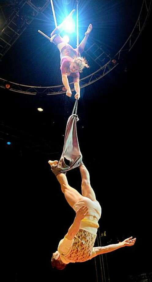 Two acrobats of Australia's internationally acclaimed circus company, Circus Oz, perform their trapeze act during a rehearsal of their new production in the lead up to the opening night, in Melbourne on June 16, 2010.  One of the very first 'new' or 'contemporary' circuses without animals, it predates most other nouveau cirque troupes and predates Cirque du Soleil by about six years.  Circus Oz has performed in 26 different countries, across five continents to over two million people. They have broken box office records at the Edinburgh Fringe Festival and represented Australia at scores of international festivals. Photo: William West, AFP / Getty Images