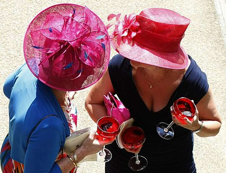 Two women racegoers drink champagne in the sunshine, on the first day of the Royal Ascot horse racing meeting at Ascot, England , Tuesday, June, 15, 2010. Photo: Alastair Grant, AP