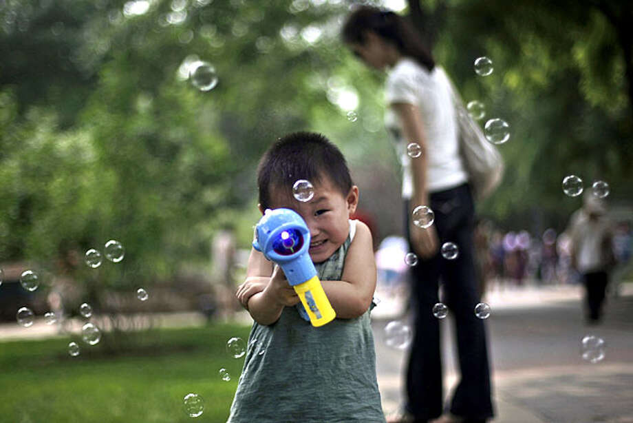 A young Chinese boy points a toy bubble gun while playing following a dragon boat race to celebrate the Duanwu Festival, also known as the Dragon Boat Festival, at Longtan park in Beijing, China, Wednesday, June 16, 2010. The festival, which falls on thefifth day of the fifth month in the Chinese calendar, commemorates the death of Qu Yuan, a famous Chinese poet from the kingdom of Chu who lived during the Warring States period. Photo: Muhammed Muheisen, AP