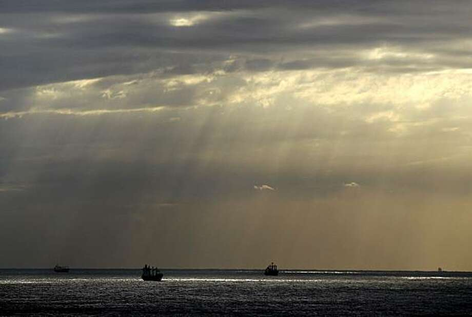 Clouds hang over Indian ocean as ships make their route, in Durban, South Africa, Tuesday, June 15, 2010. The cold weather during the first days of the Soccer World Cup will continue according the South African Weather Service. Spain plays Switzerland onWednesday in a group H game of the World Cup Soccer in this city. Photo: Thanassis Stavrakis, AP