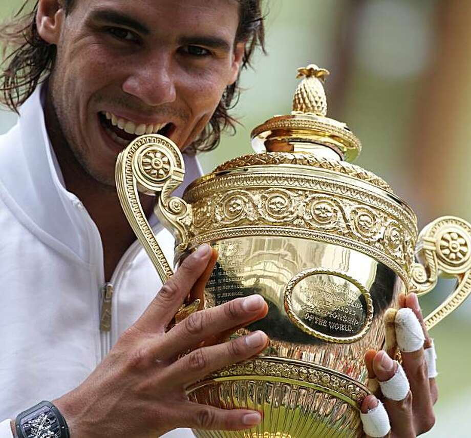 Rafael Nadal bites the trophy, after defeating Tomas Berdych in the men's singles final on the Centre Court at the All England Lawn Tennis Championships at Wimbledon, Sunday, July 4, 2010. Photo: Alastair Grant, AP