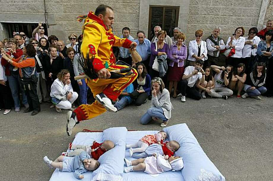 A man dressed up as the devil jumps over babies lying on a mattress in the street during the 'El Salto del Colacho' (the jump of the devil) to mark the Corpus Christi feast in Castrillo de Murcia, near Burgos, on June 6, 2010. Photo: Cesar Manso, AFP / Getty Images