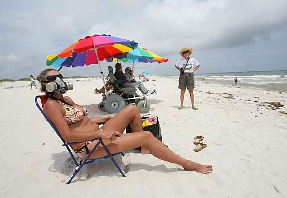 Sonja Daniel, who has a house on the Fort Morgan Peninsula, wears a mask Sunday, June 6, 2010 as she sunbathes on the beach of the Bon Secour National Wildlife Refuge in Baldwin County, Ala. Cleanup crews were working Sunday to remove tar balls and oily patches from the shoreline as managers at the refuge readied plans to construct dunes and berms to protect sensitive lagoons and wetlands. Photo: Kate Mercer, Mobile Press Register