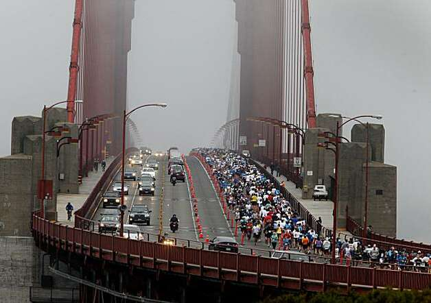 Runners crowded into the northbound lanes of the Golden Gate Bridge which they shared with regular Sunday morning traffic.The annual San Francisco Marathon started at 5:30 am Sunday July 25, 2010 and attracted over 25,000 runners on a cool, foggy summer morning. Photo: Brant Ward, The Chronicle
