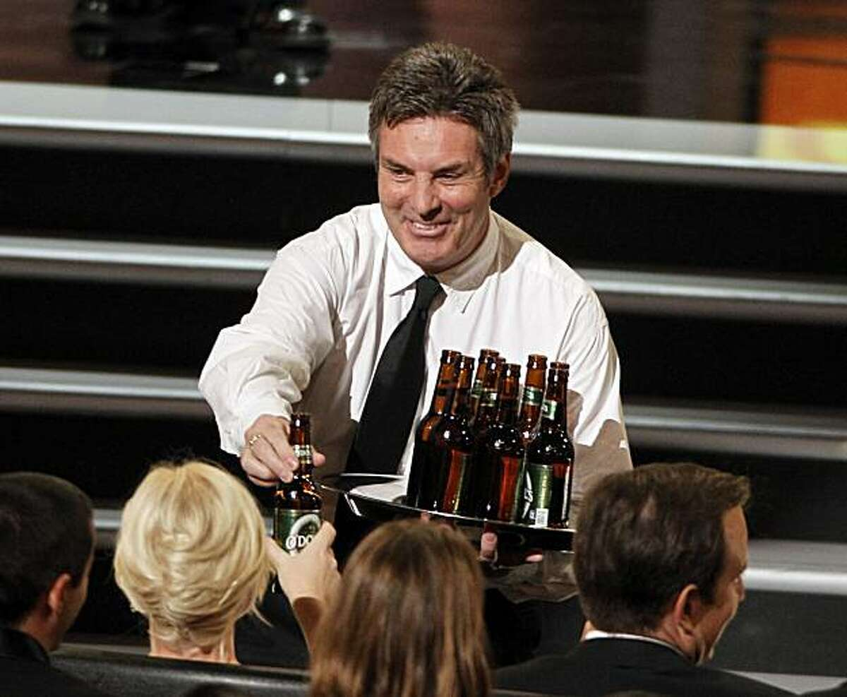 A waiter hands a non-alcoholic beer to the audience, including Amy Poehler, left, as Ricky Gervais presents the award for outstanding directing for a variety, music, or comedy specialduring the 62nd Primetime Emmy Awards Sunday, Aug. 29, 2010, in Los Angeles.