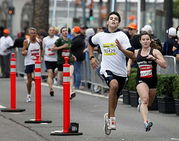Two runners sprinted to the finish for the 5K and Progressive marathon running lot. The annual San Francisco Marathon started at 5:30 am Sunday July 25, 2010 and attracted over 25,000 runners on a cool, foggy summer morning. Photo: Brant Ward, The Chronicle