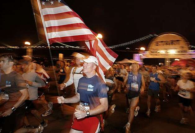 A man named Kirby carried an American flag as he started his run on the Embarcadero. The annual San Francisco Marathon started at 5:30 am Sunday July 25, 2010 and attracted over 25,000 runners on a cool, foggy summer morning. Photo: Brant Ward, The Chronicle