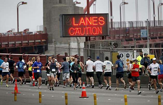 Runners began and finished their run across the Golden Gate Bridge in two lanes next to each other. The annual San Francisco Marathon started at 5:30 am Sunday July 25, 2010 and attracted over 25,000 runners on a cool, foggy summer morning. Photo: Brant Ward, The Chronicle