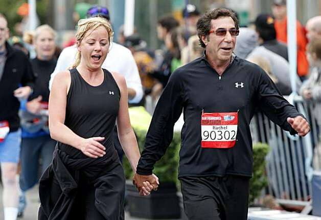 An unidentified couple dressed in black proudly hit the finish line, hands held. The annual San Francisco Marathon started at 5:30 am Sunday July 25, 2010 and attracted over 25,000 runners on a cool, foggy summer morning. Photo: Brant Ward, The Chronicle