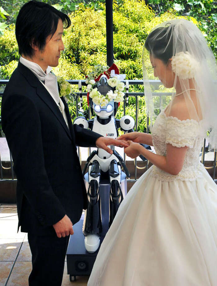 Bride Satoko Inouye, 36, puts a ring on a finger of her groom Tomohiro Shibata 42, as I-Fairy, a four-foot tall seated robot, wearing a wreath of flowers, directs their wedding ceremony at a Tokyo restaurant Sunday, May 16, 2010. The wedding was the firsttime a marriage had been led by a robot, according to manufacturer Kokoro Co. Photo: Itsuo Inouye, AP