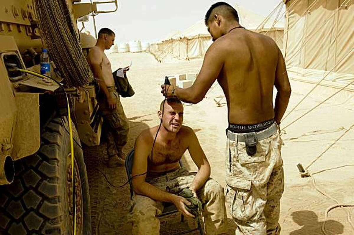 US Marine Lance Corporal Anthony Redhouse (R) 1st Combat Engineering Battalion shaves the hair of Corporal Michael Grinstead (C sitting) at Camp Dwyer in Helmand Province on July 24, 2009. About 4,000 US Marines are battling insurgents in a massive offensive launched in the south early this month to clear Taliban militants out of strongholds ahead of presidential and provincial council elections scheduled for August 20. TOPSHOTS/AFP PHOTO/Manpreet ROMANA (Photo credit should read MANPREET ROMANA/AFP/Getty Images)
