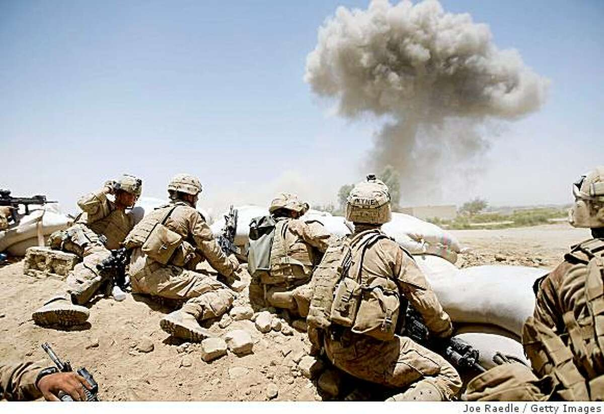 MAIN POSHTEH, AFGHANISTAN - JULY 3: U.S. Marines from 2nd Marine Expeditionary Brigade, RCT 2nd Battalion 8th Marines Echo Co. take cover as a 500 lb bomb explodes on a compound after the Marines took two days of enemy fire from the position on July 3, 2009 in Main Poshteh, Afghanistan. The Marines are part of Operation Khanjari which was launched to take areas in the Southern Helmand Province that Taliban fighters are using as a supply route and to help the local Afghan population prepare for the upcoming presidential elections. (Photo by Joe Raedle/Getty Images)