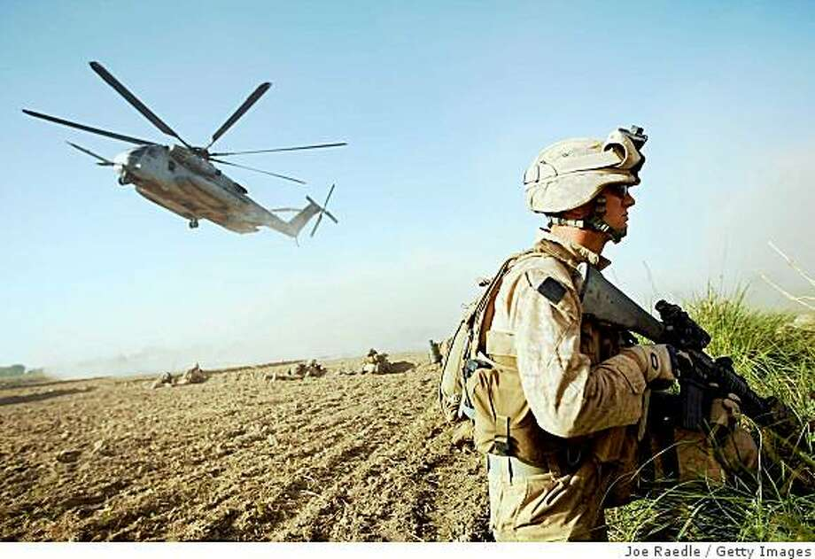 MAIN POSHTEH, AFGHANISTAN - JULY 2:  U.S. Marines from 2nd Marine Expeditionary Brigade, RCT 2nd Battalion 8th Marines Echo Co. take up defensive position as more are flown in by helicopter during the start of Operation Khanjari on July 2, 2009 in Main Poshteh, Afghanistan . The Marines are part of an operation to take areas in the Southern Helmand Province that Taliban fighters are using as a resupply route and to help the local Afghan population prepare for the upcoming presidential elections.  (Photo by Joe Raedle/Getty Images) Photo: Joe Raedle, Getty Images