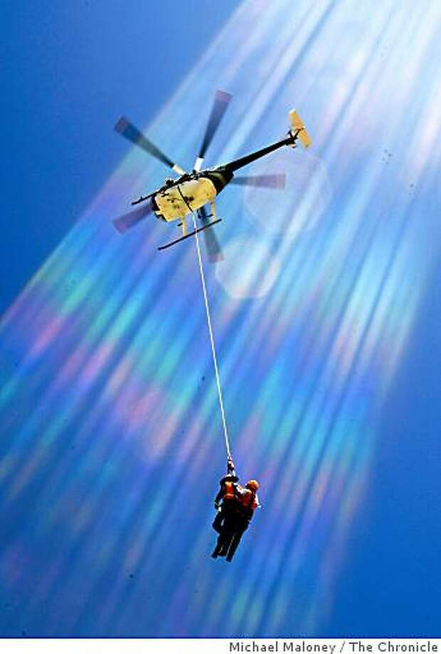 PG&E linemen dangle from a helicopter during a training session where they learned how to be transported  by helicopter to transmission towers at the PG&E training center in Livermore, Calif., on Sept. 3, 2008. The lines are flare caused by reflections of the sun off the lens. Photo: Michael Maloney, The Chronicle