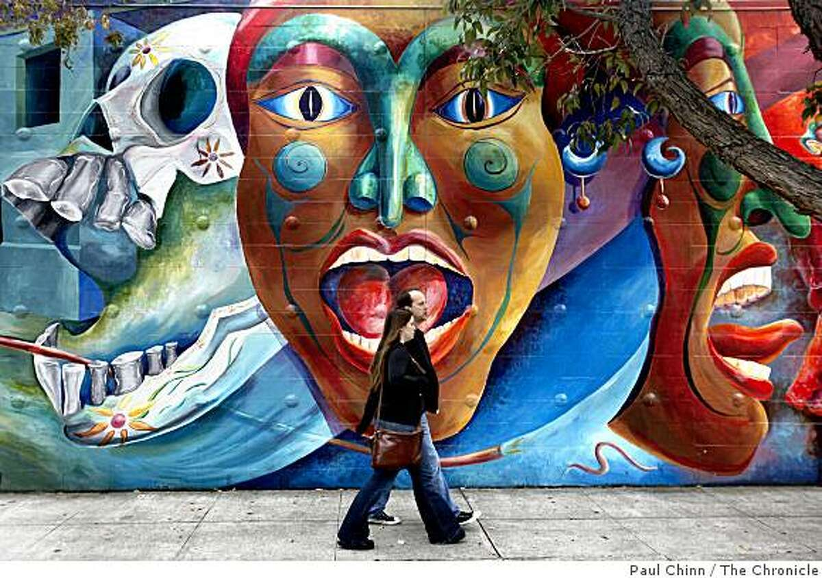 A couple walks past a Carnaval mural painted by the Precita Eyes Muralists on Harrison Street in San Francisco, Calif., on Saturday, May 23, 2009.