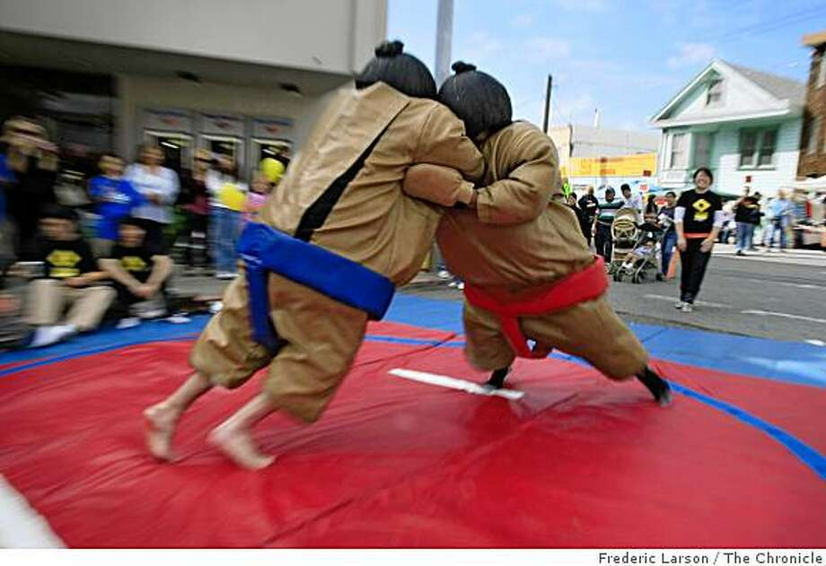 Dennis Bonilla and James Aliberi sumo wrestles each other in a full Japanese dress as both of them get into the spirit of the festivities at the Excelsoir Street Fair in San Francisco, Calif., on October 5, 2008. Photo: Frederic Larson, The Chronicle