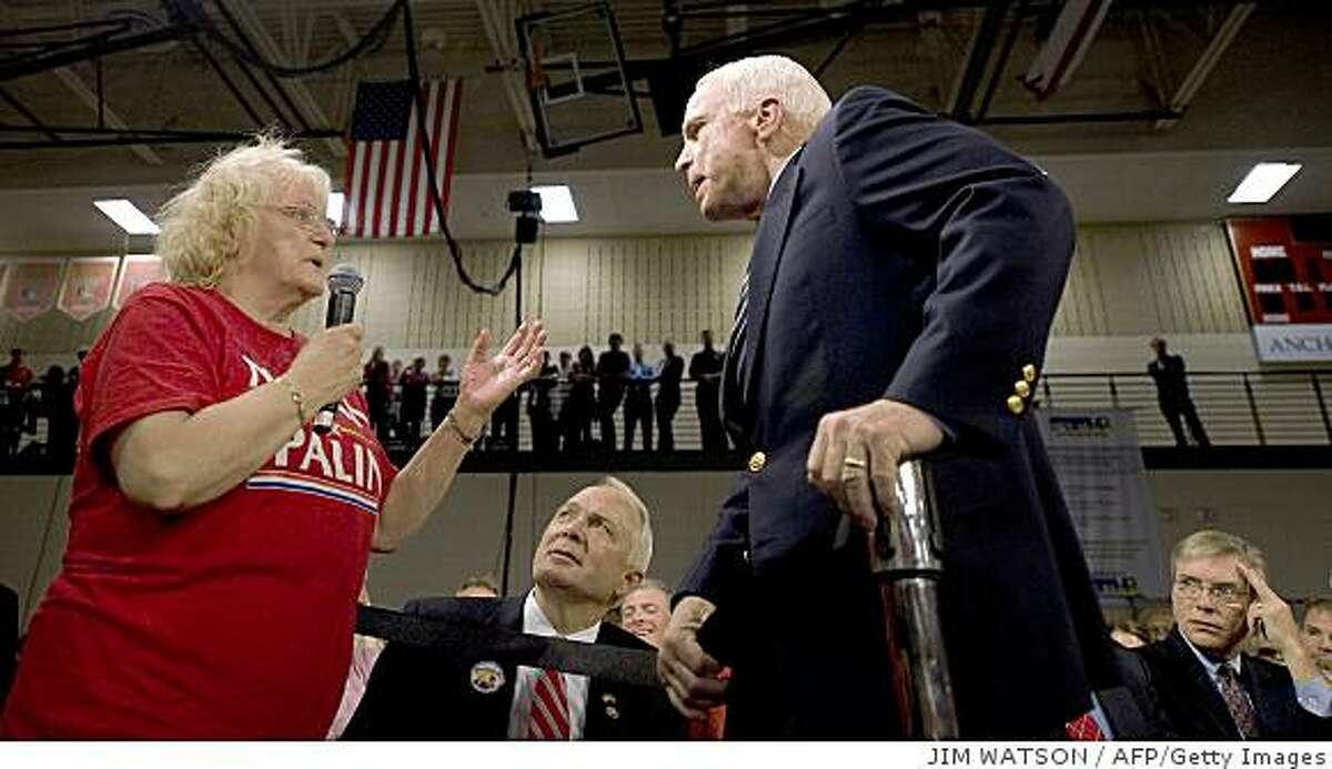 """US Republican presidential candidate Senator John McCain (R) takes a question from a supporter (L), who called US Democratic presidential candidate Barack Obama an Arab, during a town hall meeting in Lakeville, Minnesota, October 10, 2008. McCain urged his supporters to stop hurling abuse against Barack Obama at his rallies, saying he admired and respected his Democratic rival. The stream of vicious attacks against Obama, who has left McCain trailing in the polls ahead of the November 4 vote, was ramped up at the weekend by Palin who accused the Chicago senator of """"palling around with terrorists."""""""