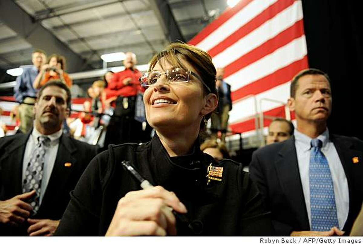 Republican Vice Presidential candidate Alaska Governor Sarah Palin greets supporters at a welcome home rally at the airport in Fairbanks, Alaska on September 10, 2008. Alaska officials fired barbs at state governor Sarah Palin September 10, trying to burst the bubble the Republican Party has been riding on since her surprise nomination two weeks ago as John McCain's running mate. AFP PHOTO Robyn BECK (Photo credit should read ROBYN BECK/AFP/Getty Images)