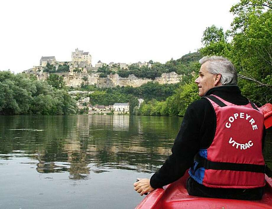 Canoeists get a dramatic view of the French village of Beynac as it tumbles down a steep hill from its majestic castle to the Dordogne River. Photo: Rick Steves