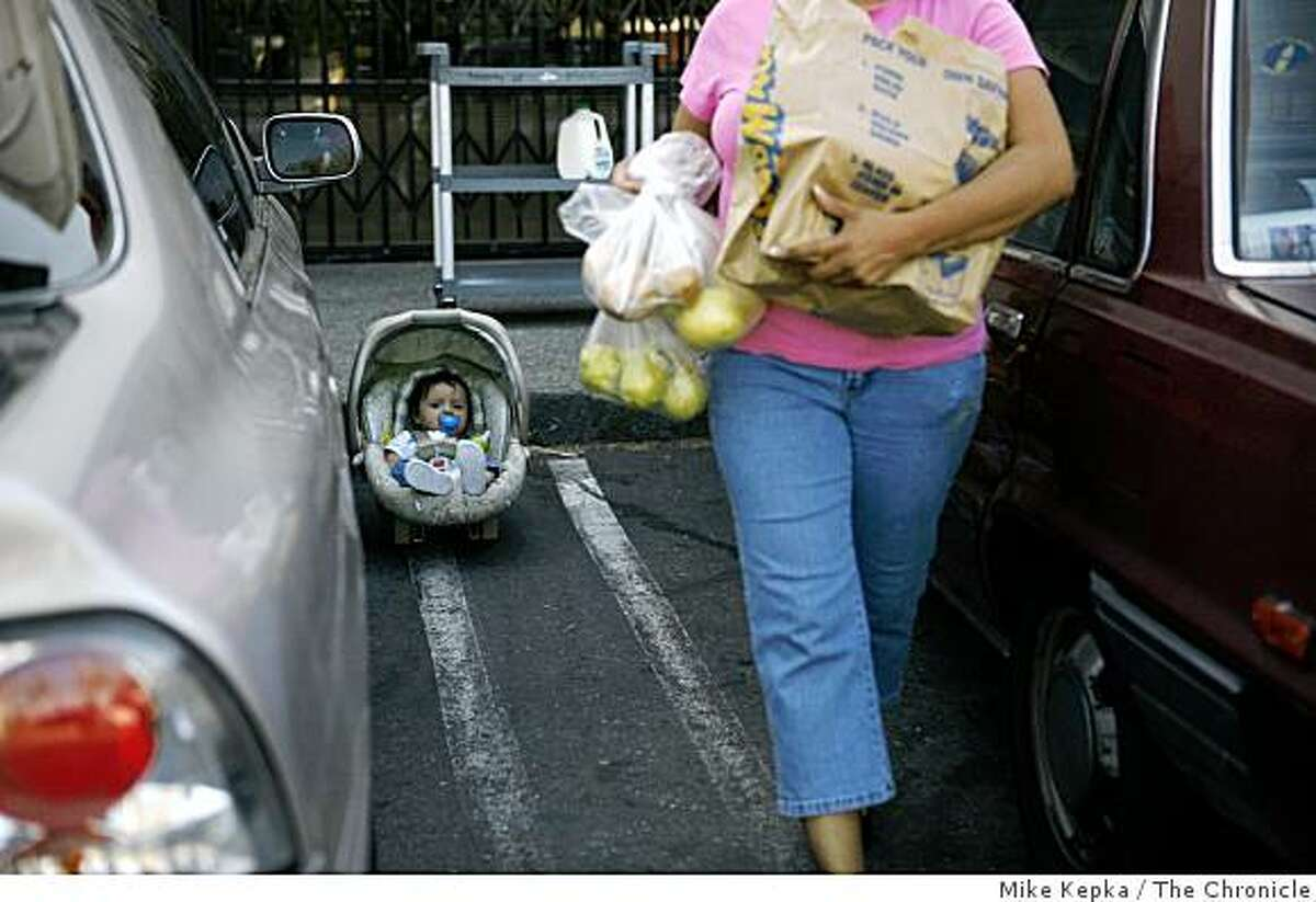 As her son Gilberto Garcia, 6-months, wathes from his car seat, Senobia Garcia, of Pittsburg, Calif., loads bags of food to her car at the Monument Crisis Center on Monday, Sept. 29, 2008 in Concord, Calif. Last week the center's shelves were almost completely empty. Two days later, after a cry for help to the community they were back in business ready to resupply food for the 6,000 people who come to them on a monthly basis.